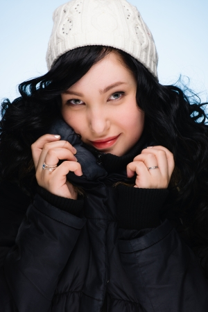 Beautiful girl wearing stocking cap, light blue background, vertical format photo
