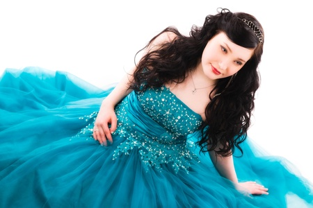 Beautiful girl wearing a prom dress, she is sitting on the ground, horizon format