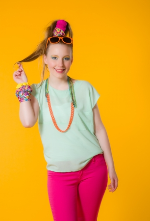 Happy girl with colorful clothes, yellow background photo