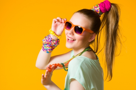 Smiling girl with colorful clothes wearing sunglasses, yellow background Stock Photo
