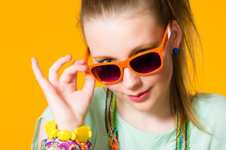 Beautiful girl wearing sunglasses, yellow background, horizon format photo