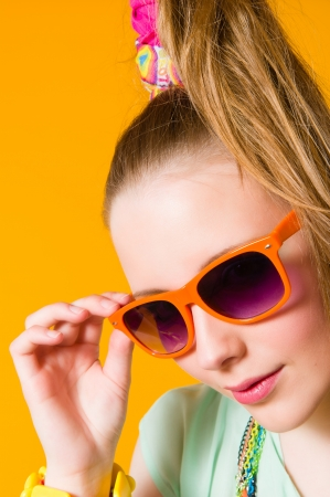 Beautiful girl wearing sunglasses, yellow background, vertical format photo