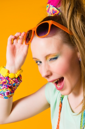 Beautiful girl wearing sunglasses, expressing faces, yellow background Stock Photo - 20236943