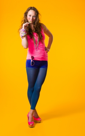 Beautiful girl wearing colorful clothes, yellow background photo