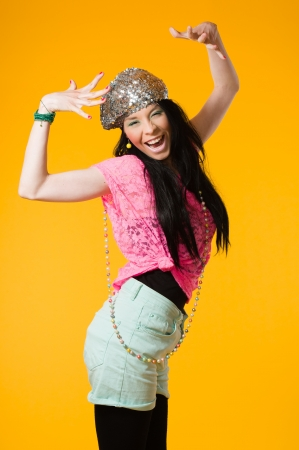 Beautiful expressing girl wearing colorful clothes, yellow background photo
