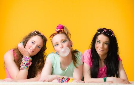 goma de mascar: Tres chicas se divierten juntos, fondo amarillo
