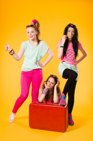 Three girls hitchhike together, red suitcase, yellow background Stock Photo - 20236930