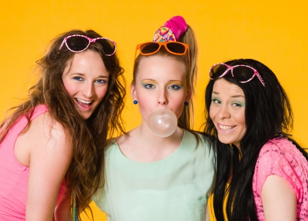 Three girls are having fun together, yellow background photo