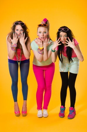 Three girlfriends on leisure wear, girls shows varnished nails photo