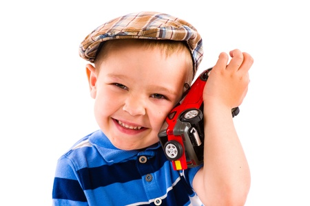 Little boy plays with red toy car, white background