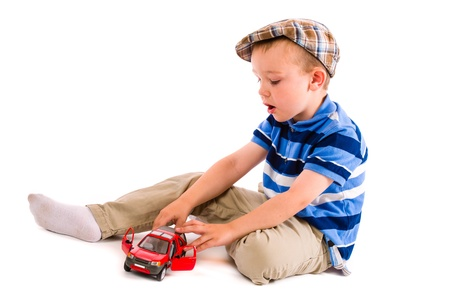 toy cars: Little boy plays with red toy car, white background Stock Photo