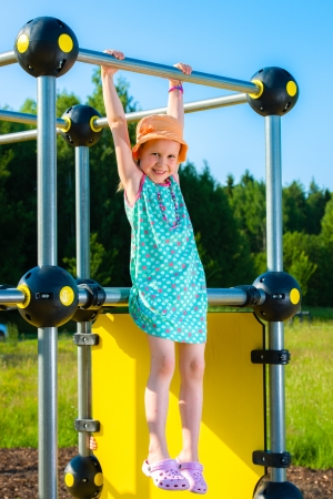 jungle gym: Young girl hangs on the jungle gym, sunny day