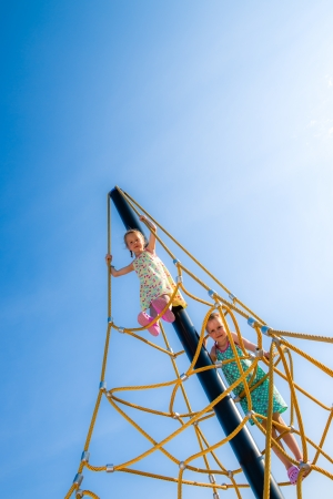 jungle gym: Two young girls on the jungle gym, sunny day Stock Photo