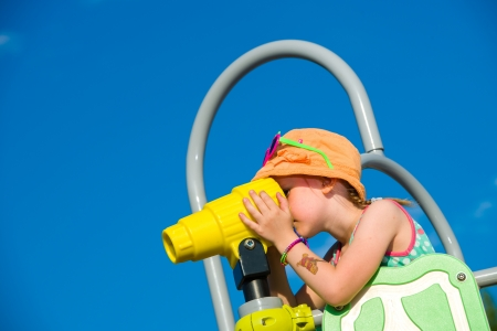 jungle gym: Young girl use binoculars on jungle gym, sunny day
