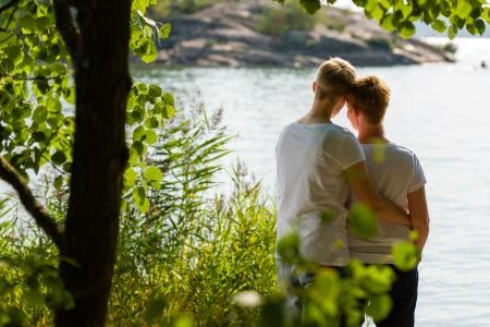 gay love: Pareja de lesbianas encantadora juntos, d�a soleado, el mar de fondo