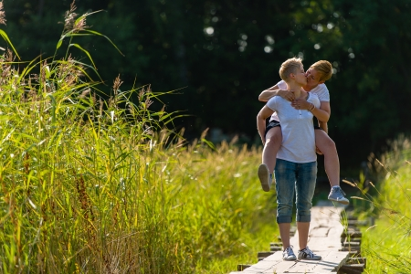 beautiful lesbian: Lovely lesbian couple are piggyback together, sunny day Stock Photo