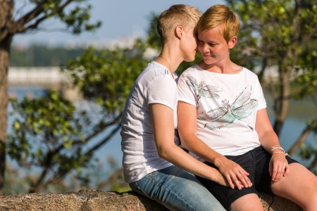 Lovely lesbian couple together in privacy, sunny summer day