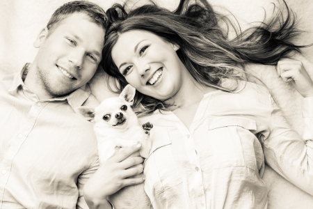 Lovely attractive couple and dog together, studio shot, white background photo