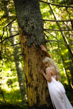 Beautiful woman wearing white garment and lean against the old spruce photo