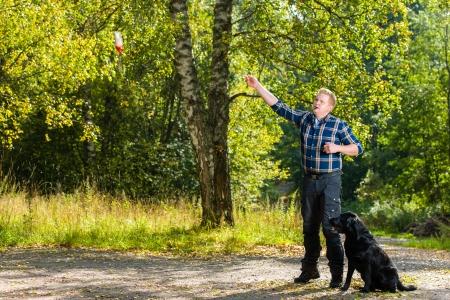 dutiful: Dog owner trains his labrador retriever on outdoor, dog sits on alongside, horizon format