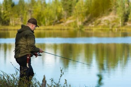 Fisherman on the little lake, beautiful landscape on background