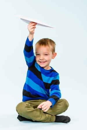 Happy boy playing with paper airplane in studio, light blue background photo