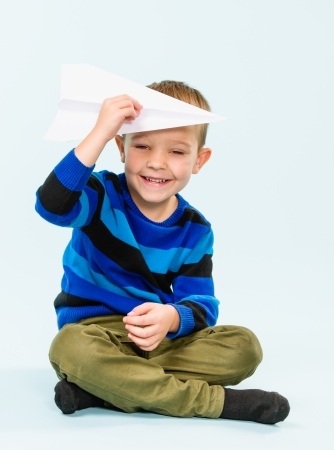 Happy boy playing with paper airplane in studio, light blue background Stock Photo - 22442523