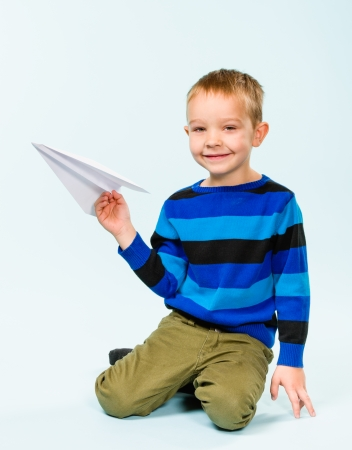 Happy boy playing with paper airplane in studio, light blue background Stock Photo - 22442525