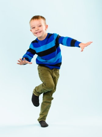 niños bailando: Niño pequeño juguetón en estudio, fondo azul claro Foto de archivo