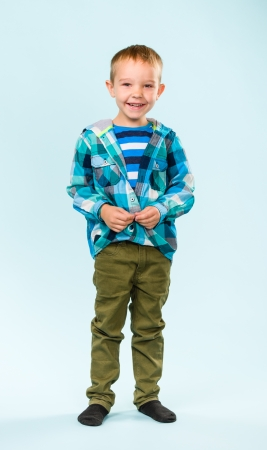 gratified: Playful little boy on studio, light blue background Stock Photo