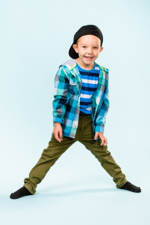 Playful little boy wearing peaked cap on studio, light blue background Stock Photo - 22442536