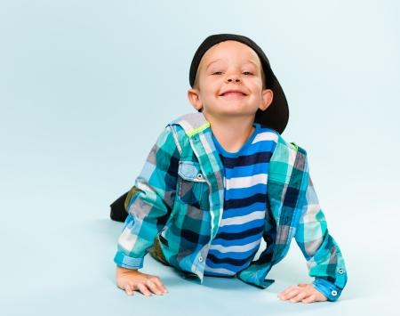 gratified: Playful little boy wearing peaked cap on studio, light blue background