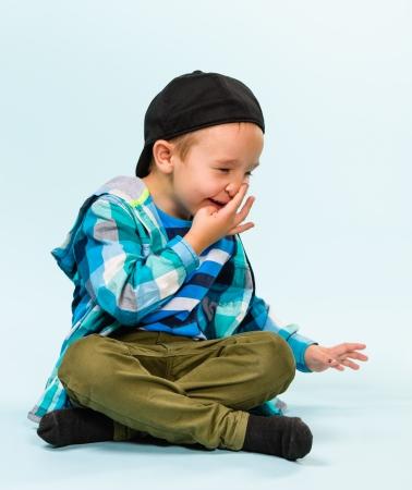 Playful little boy wearing peaked cap on studio, light blue background Stock Photo - 22442542