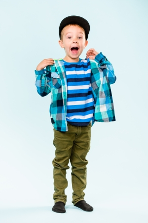 Playful little boy wearing peaked shouting on studio, light blue background photo