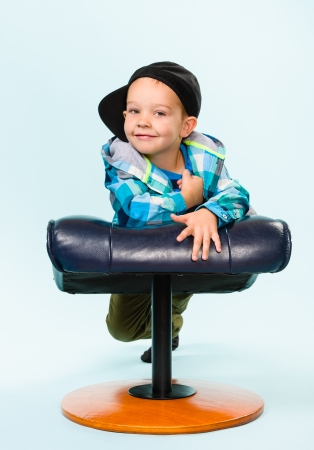 Little boy on posing with a footstool, studio shot and light blue background Stock Photo - 22442544