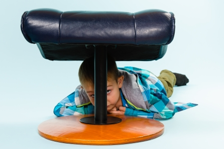footstool: Little boy on posing with a footstool, studio shot and light blue background