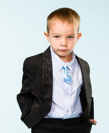 Handsome little boy posing on studio, light blue background photo