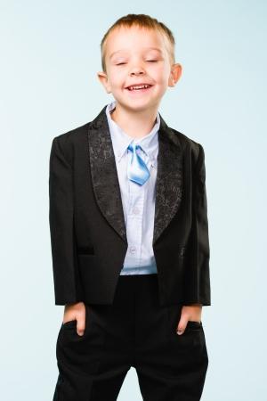 gratified: Handsome little boy posing on studio, light blue background Stock Photo