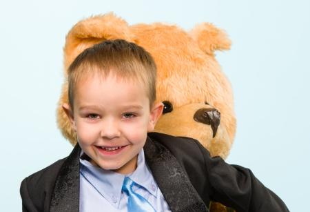 Little boy posing and playing with a teddy bear on studio, light blue background Stock Photo - 22442570
