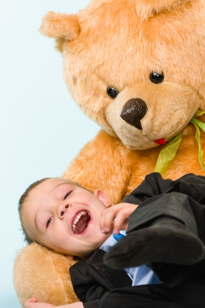 Little boy posing and playing with a teddy bear on studio, light blue background photo