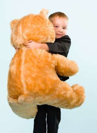 Little boy posing and playing with a teddy bear on studio, light blue background Stock Photo - 22442576