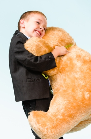 Little boy posing and playing with a teddy bear on studio, light blue background Stock Photo - 22442577