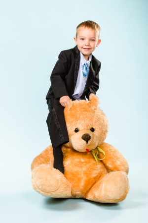 Little boy posing and playing with a teddy bear on studio, light blue background Stock Photo - 22442579