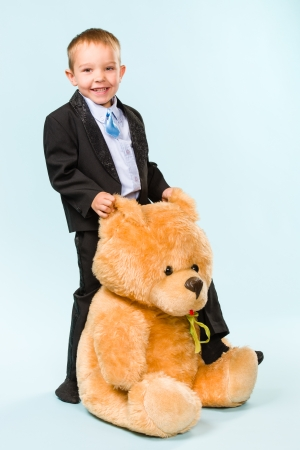 gratified: Little boy posing and playing with a teddy bear on studio, light blue background