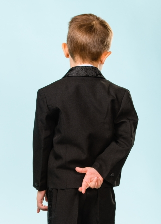 Boy have fingers crossed behind back, light blue background Stock Photo