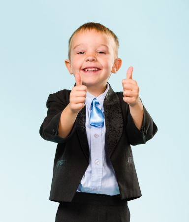 gratified: Smiling little boy wearing suit, thumbs up, studio shot and light blue background