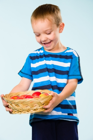 Little boy on striped t-shirt, fruit basket, studio shot and light blue background Stock Photo - 22442585
