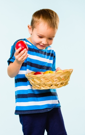 gratified: Little boy on striped t-shirt, fruit basket, studio shot and light blue background Stock Photo