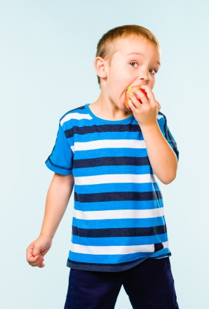 gratified: Little boy on striped t-shirt eating apple, studio shot and light blue background