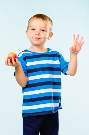 Little boy on striped t-shirt eating apple, studio shot and light blue background photo